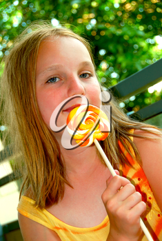 Young girl holding a big colorful lollipop candy