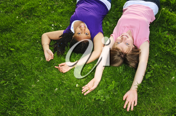 Two teenage girls laying on grass arms outstretched