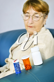Elderly woman looking at pill bottles with medication