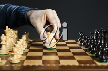 Hand moving a knight chess piece on wooden chessboard