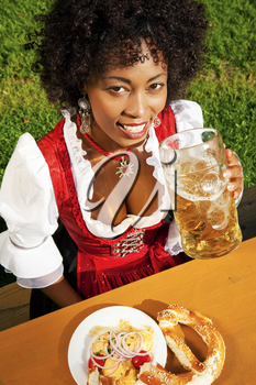 Very beautiful woman of color in traditional Bavarian costume - dirndl - drinking beer and eating pretzel and obatzter (traditional cheese)
