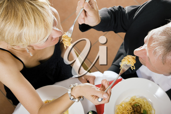 Romantic mature couple having dinner, she feeding him with delicious pasta