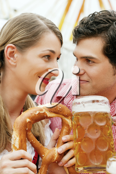 Couple in traditional German costume in a beer tent, he is having a drink, she a pretzel, scene could be located at the Oktoberfest or any Duld