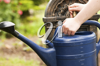 Garden scene - woman, only hands to be seen, refilling the watering pot at a tap