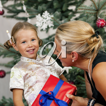 Young girl receives a gift by her mother