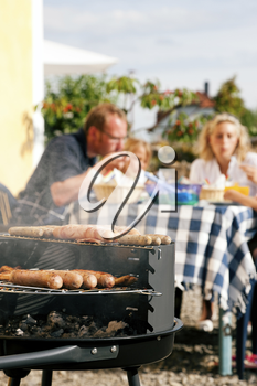 Family having a barbecue in the garden, eating (focus on barbeque grill!)