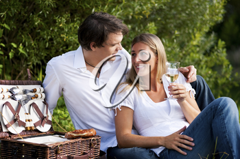 Couple sitting outdoors having a picnic with white wine