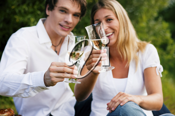 Couple in love sitting outdoors having a picnic clinking glasses and drinking white wine (focus on glasses!)