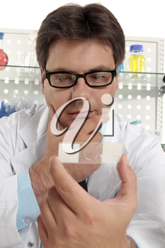 Scientist, biologist, botanist or other medical or laboratory worker holding a prepared slide and thinking.  Focus to man