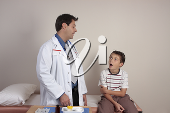 Doctor talking to a young patient who is sitting on the examination bed.  No release required for id photo.