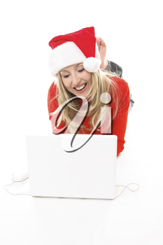 Christmas girl using a laptop to shop or browse the web online. She might also be studying chatting to friends or family  or electronic banking, etc.    She is wearing a festive santa hat and smiling.