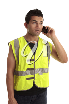 Construction worker in safety vest receives a call on a mobile phone.