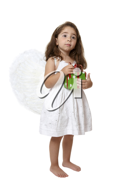Angel girl wearing white embroidered dress and feathered wings is holding a red and green Christmas or brithday  present.
