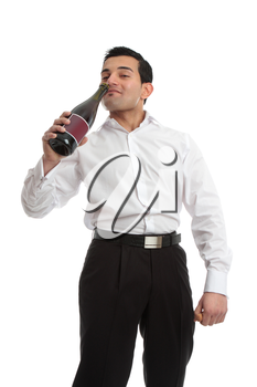 An enebriated man staggers and drinks swigging wine directly from a bottle.