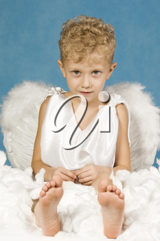 Portrait of cute boy in angel clothes sitting in cloud and looking at camera