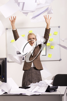 Portrait of happy businesswoman raising arms and throwing papers in office with laugh