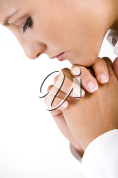 Profile of thoughtful female with her hands by face over white background