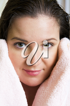 Close-up of charming woman touching her face with towel and looking at camera