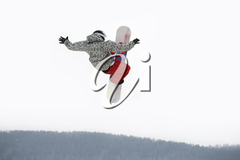 Image of courageous guy jumping on snowboarder in the air