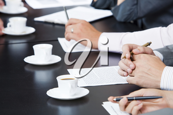 Image of businesspeople�s hands with pens, papers and cups of coffee near by