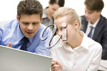 Business partners looking at laptop monitor in working environment