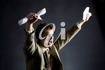 Photo of emotional businessman with papers raising his arms