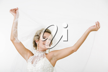 Portray of happy beautiful fiancee raising hands with veil