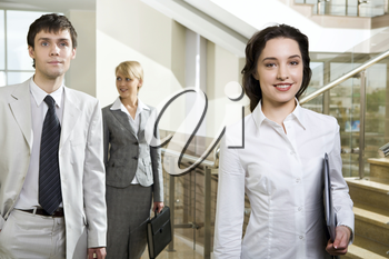 Young brunette businesswoman with the black case in her hand looking at camera, thinking businessman in white suit and cute smiling woman moving on the stair platform