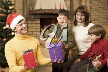 Portrait of joyful children looking at their presents surrounded by parents
