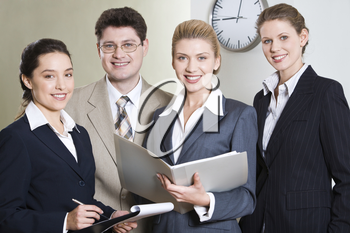 Group of four successful professionals looking at camera in the office