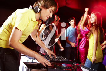 Smart deejay spinning turntables with dancing teens on background