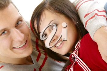 Close-up of happy young couple in embrace looking at camera
