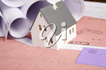 Close-up of toy house model with rolled blueprints near by