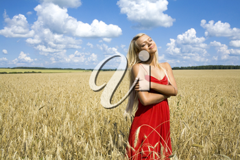 Photo of charming female in red dress standing in wheat field