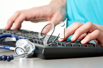 Close-up of physician hands typing with stethoscope near by