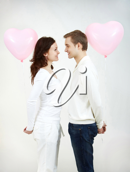 Two beautiful young people with heart-shaped balloons looking at each other