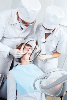 Image of  woman opening her mouth and doctor and nurse checkup her teeth