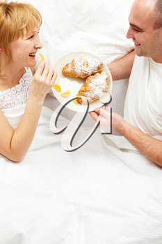 Wife and husband eating their breakfast in bed