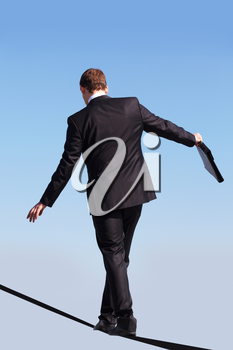Back view of contemporary businessman walking down ribbon or rope with blue sky at background