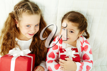 Portrait of happy girls with gifts looking at camera and smiling