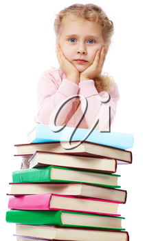 Portrait of a little girl at a heap of books