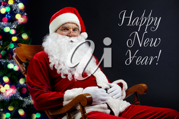 A card with Santa sitting in the armchair at the Christmas tree and the text �Happy New Year�