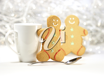 Royalty Free Photo of Gingerbread Men Beside a Cup and Spoon
