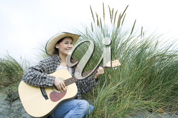 A shot of a beautiful woman playing guitar outside at the beach