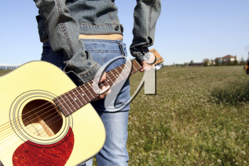 A woman holding a guitar looking at an empty field