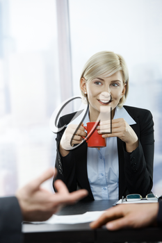 Smiling businesswoman with coffee mug sitting at table.