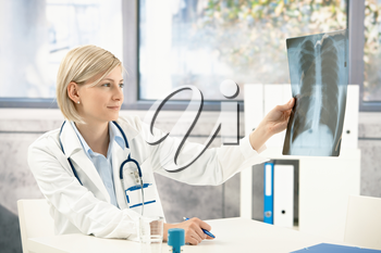 Medical doctor analysing x-ray image handheld, sitting at office desk.