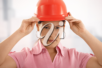 Happy female architect adjusting her hardhat, looking at camera, smiling.