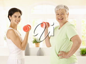 Healthy senior woman doing dumbbell exercise with personal trainer at home, smiling.