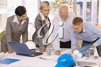 Architect team working together in office, senior designer drawing, coworkers watching.